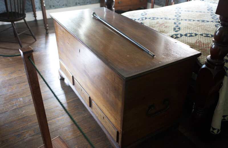 A Blanket Chest with a Cane on the Lid