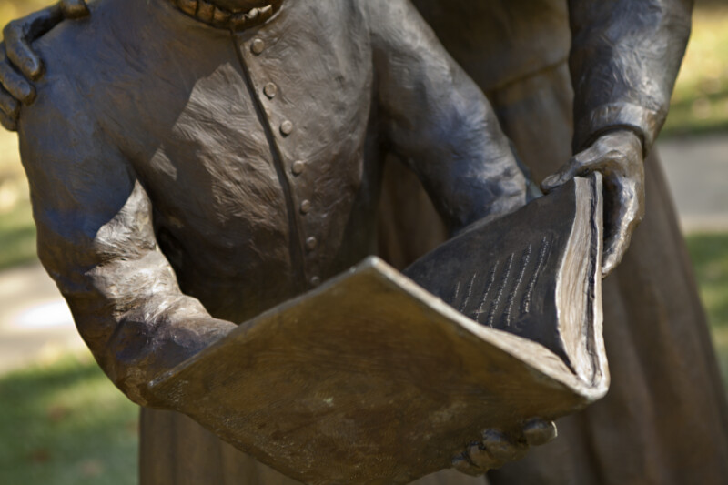 A Book in the Hands of Two Bronze Figures
