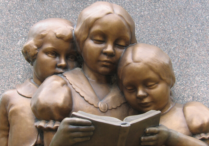 A Boy and Two Girls Reading a Book at Base of William McGuffey Memorial