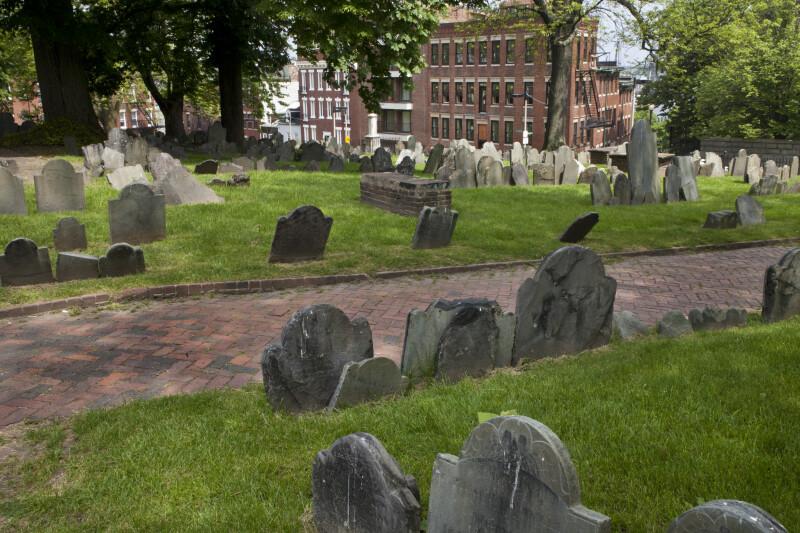 A Brick Walkway between Headstones
