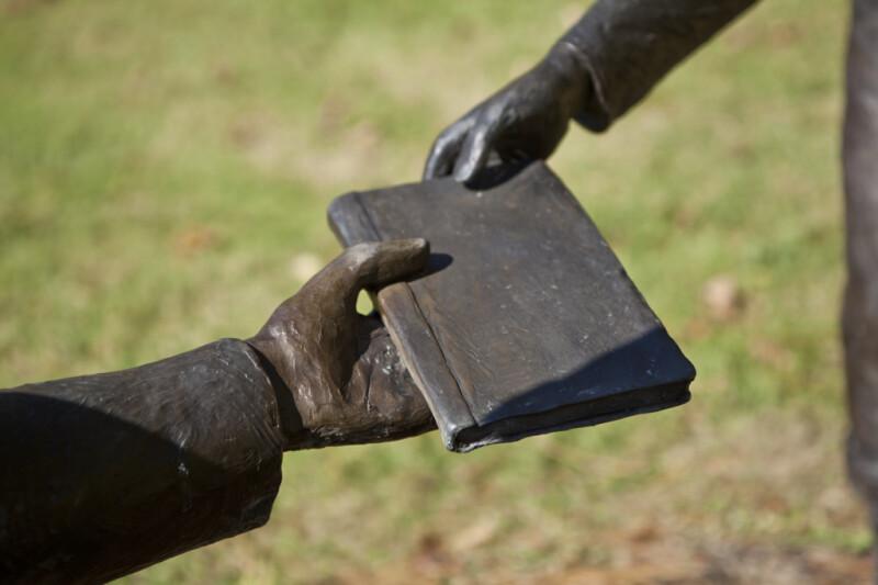 A Bronze Sculptural Representation of Two Hands Grasping a Book