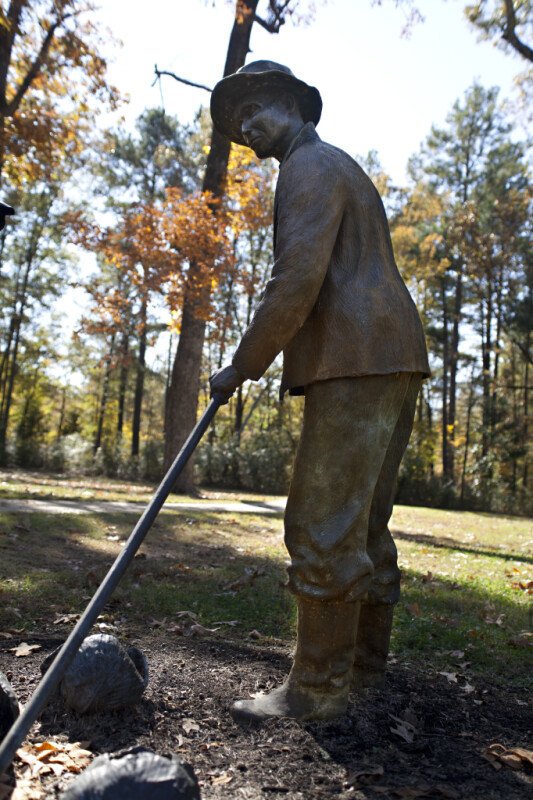 A Bronze Sculpture Depicting a Farmer with a Hoe