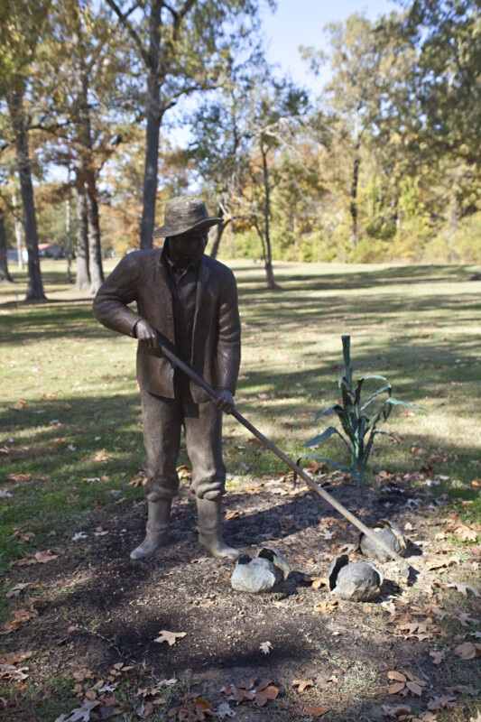 A Bronze Sculpture of a Farmer in a Public Park