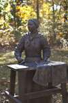 A Bronze Sculpture of a Woman Doing Laundry