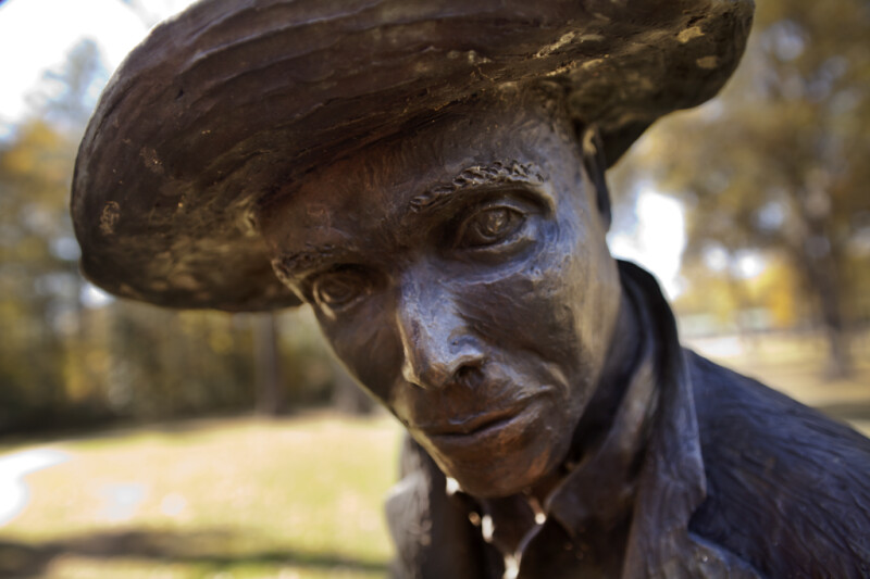 A Close-Up of the Face of a Bronze Sculpture Depicting a Farmer