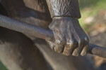 A Close-Up of the Hand of a Bronze Sculpture Depicting a Farmer