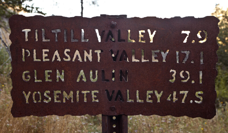A Metal Sign on a Hiking Trail with Distances to Valleys