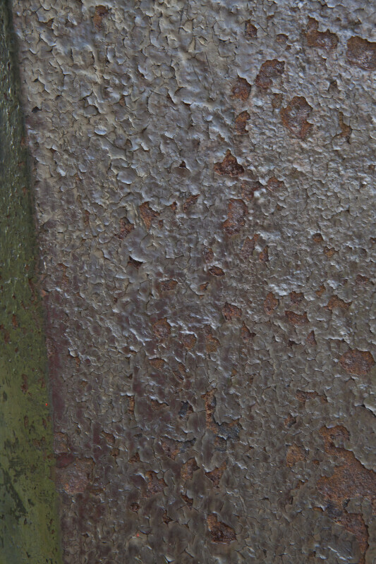 A Rusted Metal Surface with Black, Peeling Paint