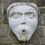 A Sculpted Face, with a Beard and Mustache, on a Masonry Wall