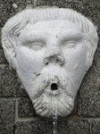 A Sculpted Face, with an Upturned Nose, on a Masonry Wall
