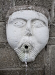 A Sculpted Face, with Round Cheeks, on a Masonry Wall