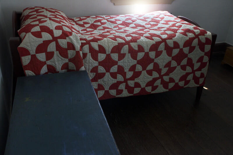 A Small Bed with a Red and White Quilt