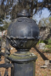 A Sphere on a Post at the Corner of a Metal Fence around a Cemetery Plot