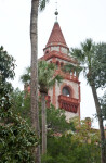 A Square Tower with a Conical Roof and Palm Trees