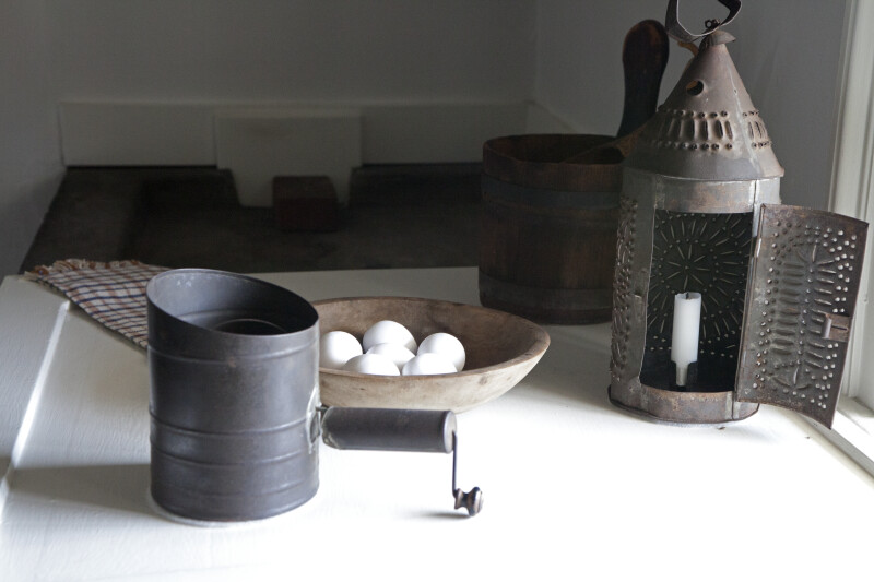 A Tin Lamp, a Flour Sifter, and a Bowl of Eggs