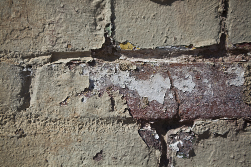A View of Paint Peeling from a Brick Wall