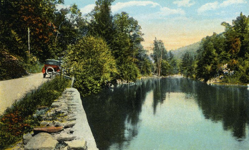 A Vintage Automobile Driving Beside a Mountain Lake