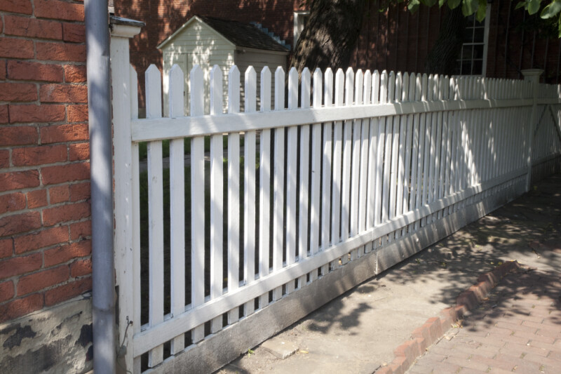 A White Picket Fence by a Brick Building