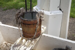 A Wooden Bucket with a Rope for a Handle