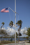 American Flag Attached to Post in Front of Palm Trees