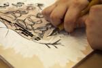 An artist carving a sintra plate.