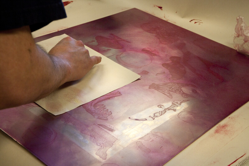 An artist paper-wiping an intaglio plate with red ink.
