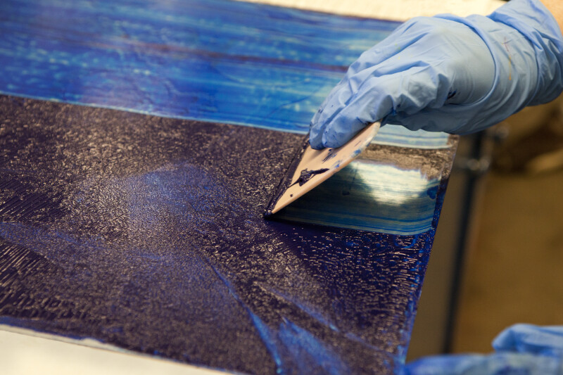 An artist scraping excess ink off of an etching plate.