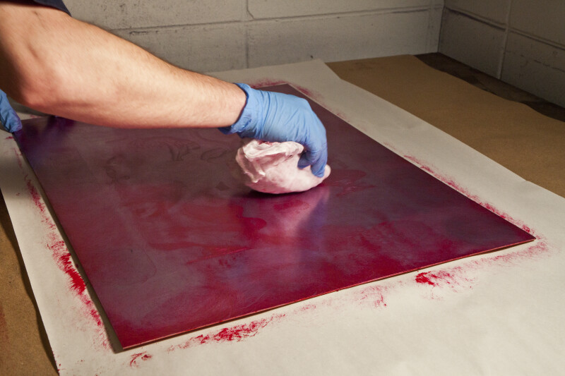 An artist wiping an etching plate with red ink.