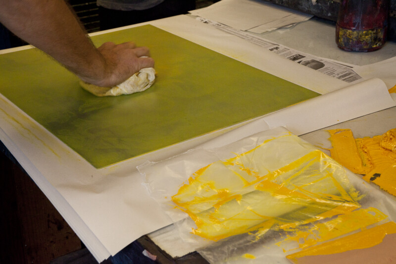 An artist wiping an etching plate with yellow ink.