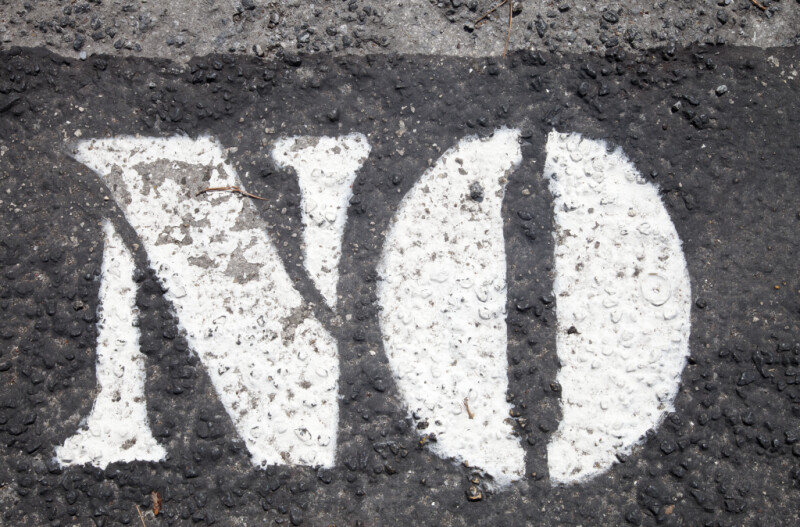 "Asphalt with ""NO"" Written in White Paint"