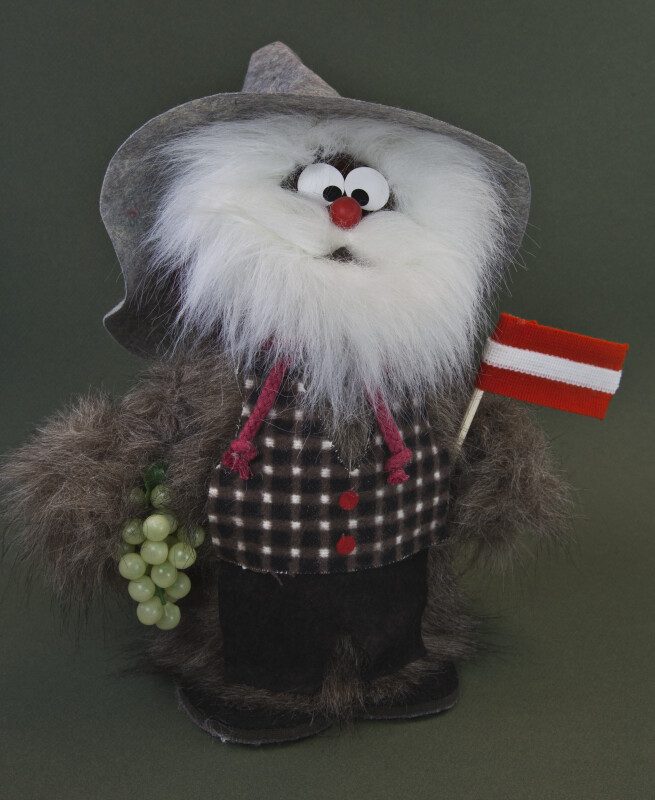 Austria Mountain Man Made from Pinecones and Fur and Holding an Austrian Flag (Full View)