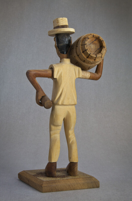 Bahamas Wood Carving a Man Holding a Keg of Rum and a Bottle (Back View)