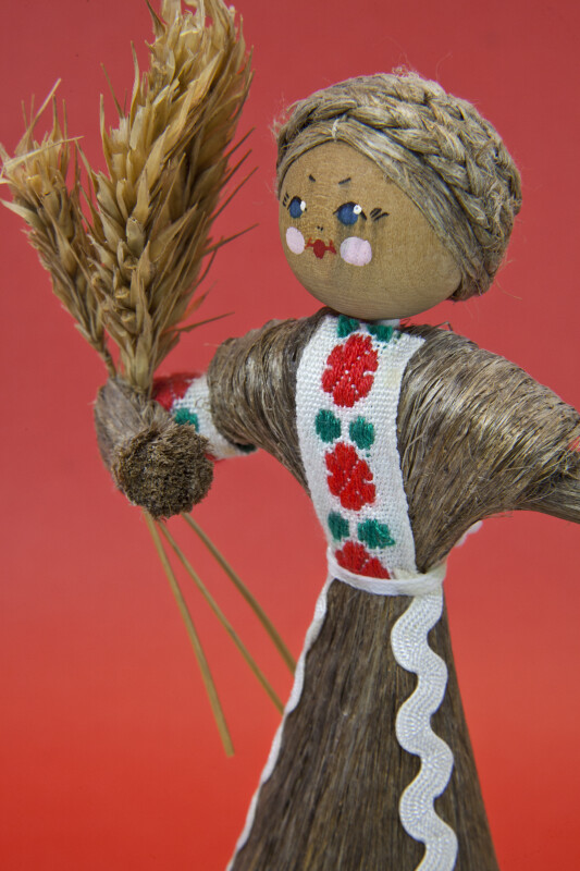 Belarus Doll with Wood Bead for Head and Hand Painted Facial Features Holding Wheat Plants (Close Up)