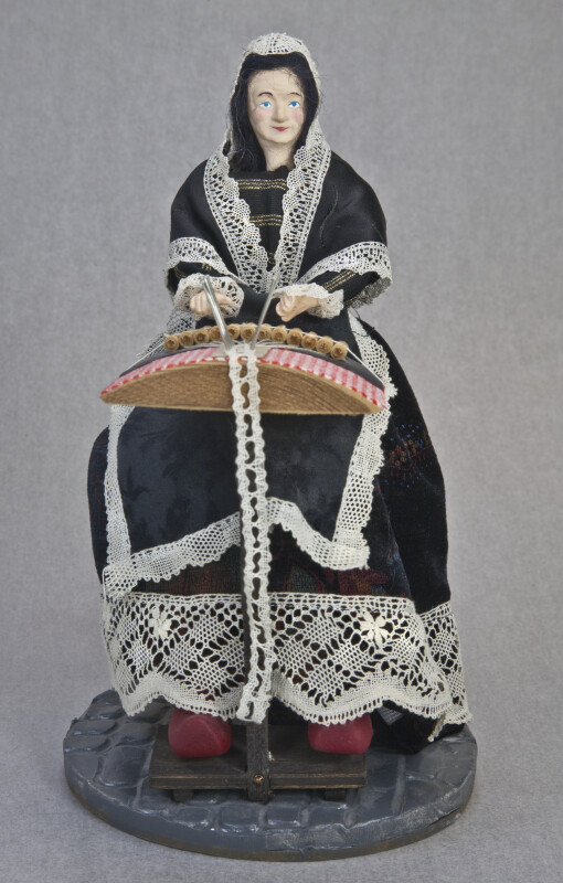 Belgium Figurine of Female Lace Maker Holding a Pillow, Bobbins, and Thread (Full View)
