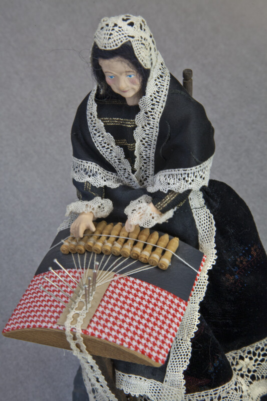 Belgium Doll Making Lace in Bruges, Belgium with Bobbins and Thread (Three Quarter Top-Down View)