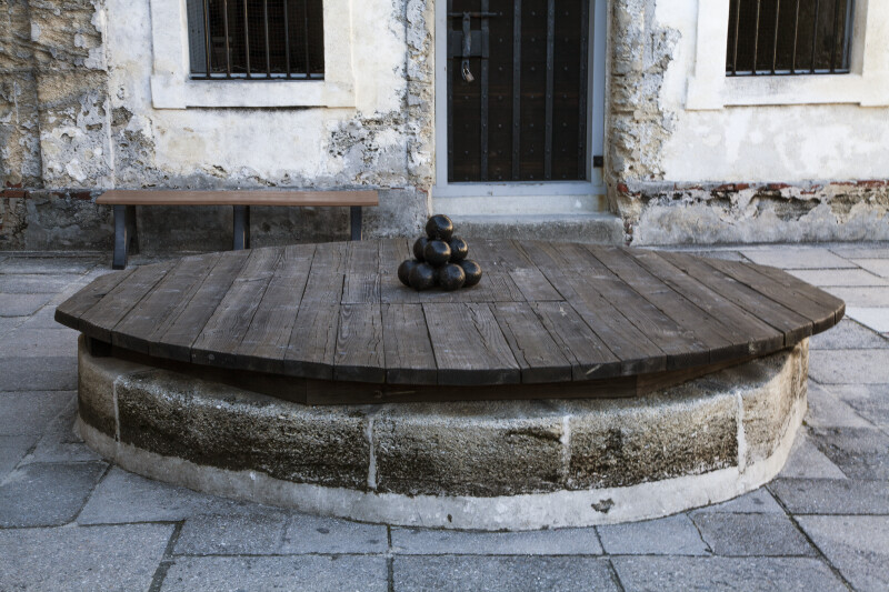 Black Cannonballs Stacked on a Wooden Covering of a Well