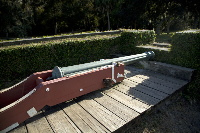 Blue Cannon on a Reddish-Brown Cannon Carriage Resting on a Wooden Firing Step