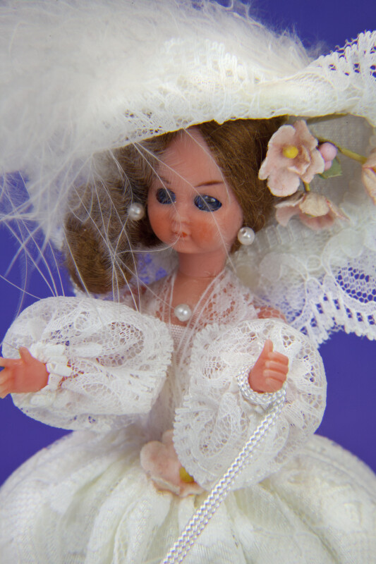 Brussels Plastic Doll with Feather Hat and Pearl Earrings (Close Up)
