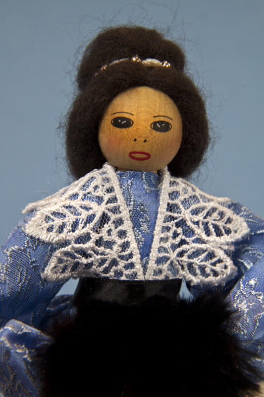 Canada Wooden Doll Dressed in Blue Brocade Dress and Holding a Fur Muff (Close Up)