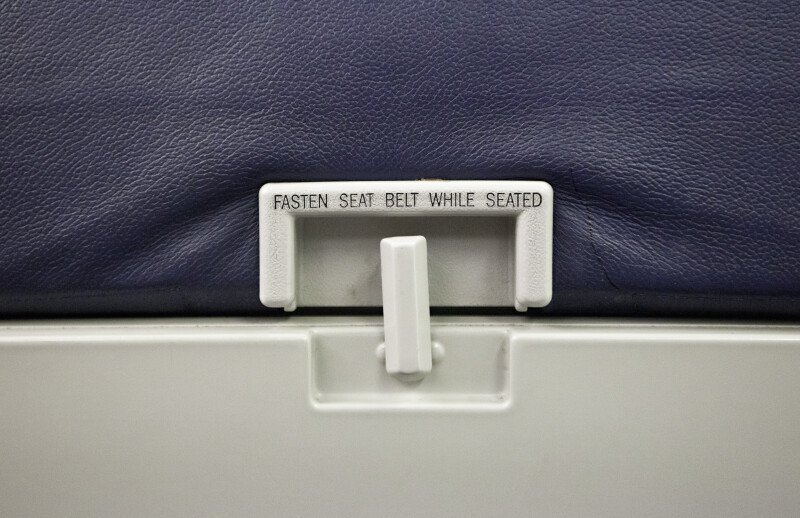 Collapsible Table and Seat Belt Warning Sign on Airplane