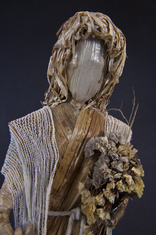 Costa Rica Female Doll with Corn Husk Face and Fiber Hair Holding Dried Flowers (Close Up)