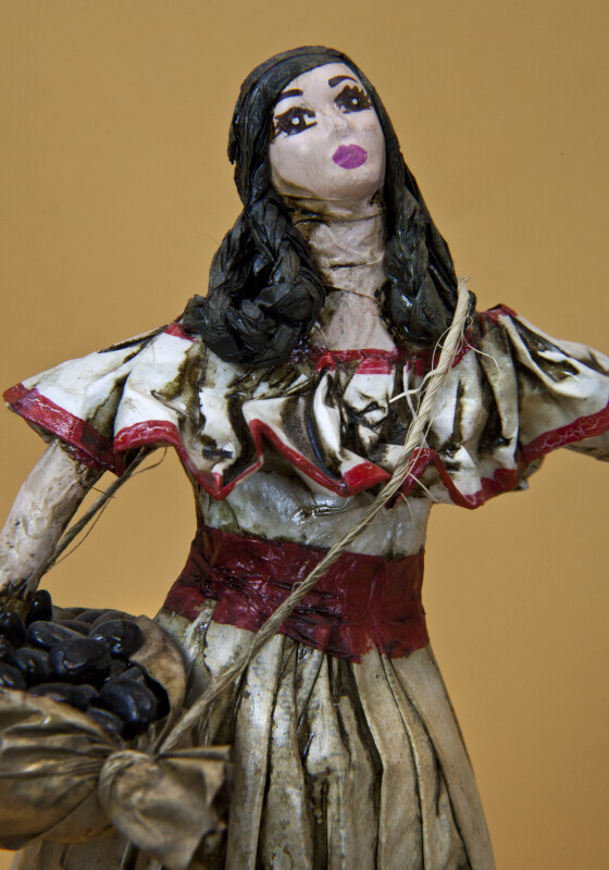 Costa Rica Female Figure Handcrafted with Paper and String, Wearing Traditional Dress While Carrying Coffee Beans (Close Up)