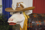 Cow Statue with Red Lipstick, Cowboy Hat, and Coat