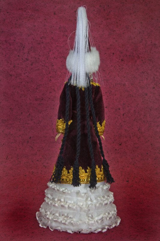 Doll Wearing Cone-Shaped Hat and Velvet Coat Trimmed in Gold (Back View)