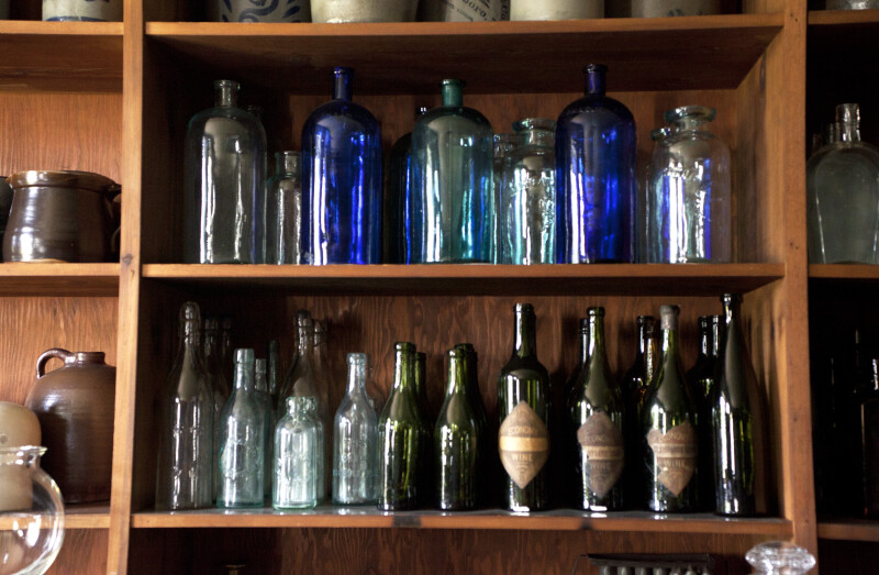 Empty Glass Bottles on Shelves