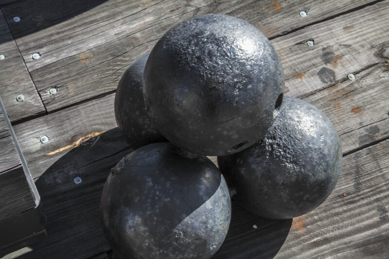 Four Cannonballs Stacked on Wooden Boards