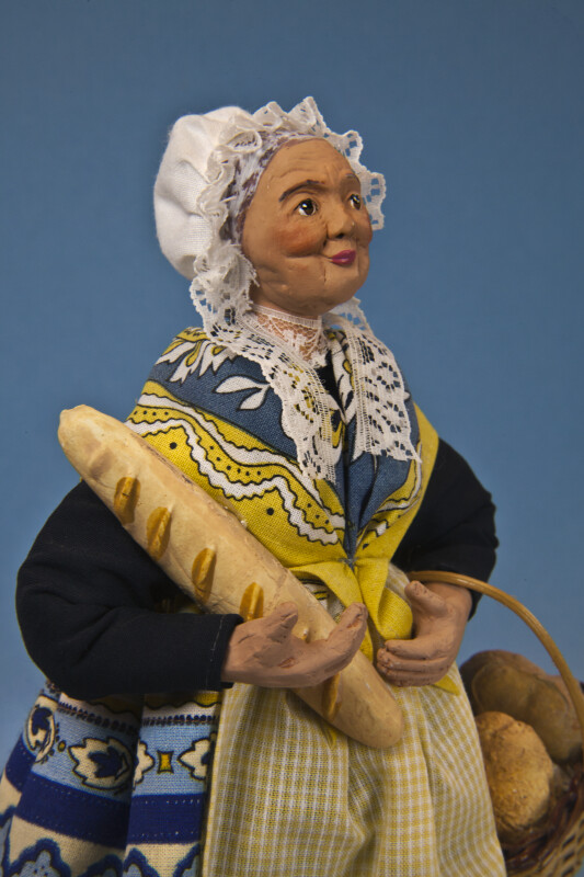 France Female Santon de Provence with Hand Painted Face and Lace Cap Holding a Baguette  (Close Up)