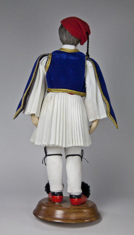 Greece Male Doll Made from Ceramic with Red Hat, Red Shoes, and Traditional Costume of Vest and Pleated Skirt (Back View)