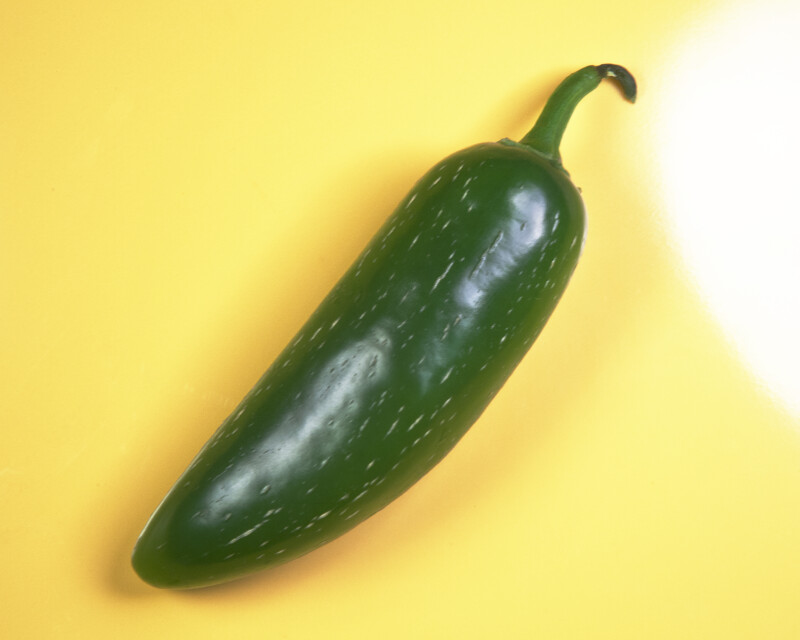 Green Chili Pepper Against Yellow Background