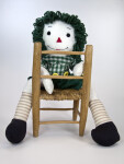 Illinois Raggedy Andy Doll with Yarn Hair Seated Backwards on a Wicker Chair (Full View)